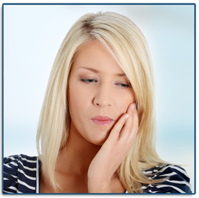 blonde woman holding the side of her jaw in need of an emergency dentist