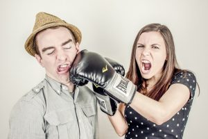Woman with boxing glove hitting man in face